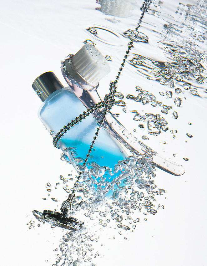 bottle wrapped in plug underwater with bubbles, underwater photography, underwater photographer, beauty photography, beauty product photographer, still life photography, David Parfitt, still-life, still-life photography, still-life photographer, still-life photographer London, David Parfitt, advertising photographer