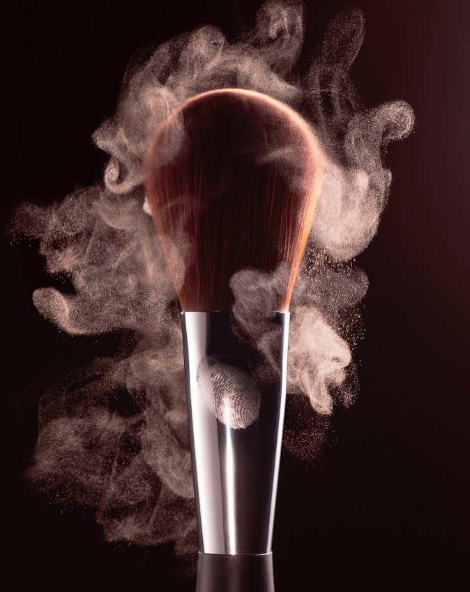 make up brush with loose powder on the bristles and in the air surrounding, still life by David Parfitt, beauty, beauty product photography, beauty still life, beauty product photographer, make up photography, powder photography, still-life photographer, still-life photographer London, David Parfitt, advertising photographer